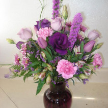 Purple roses and purple tulips with assortment of lavender in a purple vase