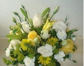 Asiatic lilies yellow and white roses and other assorted of flowers in a vase
