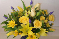 Assortment of yellow flowers with blue irises in a blue vase