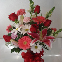 Red roses and pink lilly's with other assignments in a vase