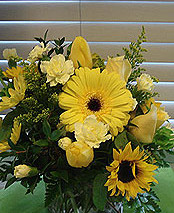 Assortment of yellow flowers in a square vase